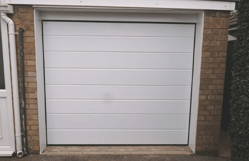 Novoferm large linear insulated sectional door in white woodgrain installed in Spalding