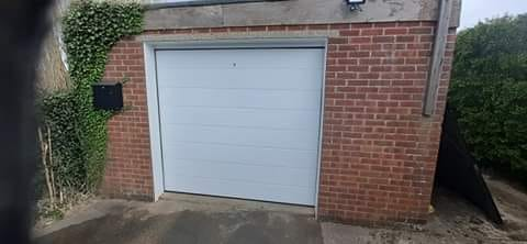 Automated insulated sectional garage door in White.