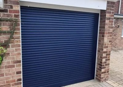 Compact roller doors in steel blue with white frames.