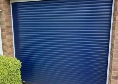 SWS compact roller door in steel blue with white frames.