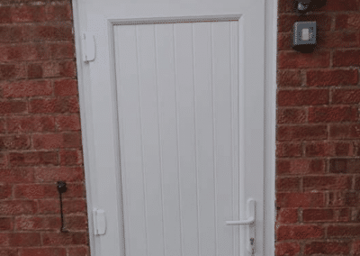 A white upvc side door with a shiplap panel installed to in Ingoldisthorpe