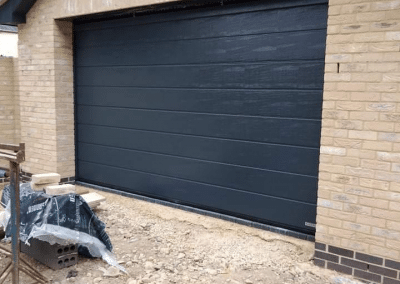 Garador medium linear insulated sectional door finished in Anthracite woodgrain.