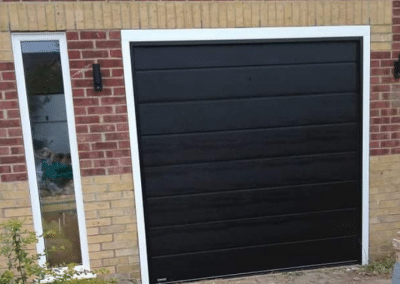 Carteck insulated centre ribbed sectional door finished in black woodgrain.